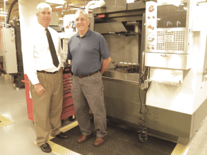Bob LePage, left, and John LaFrancis show off one of the new machines in the Smith & Wesson Technology Application Center at STCC.