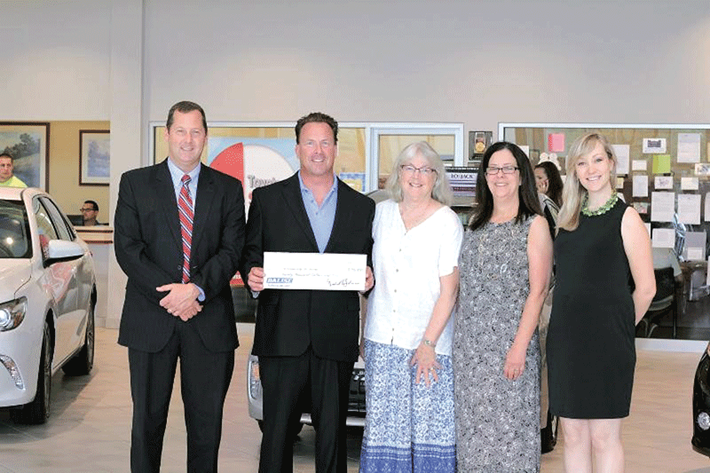 Mike Balise, second from left, presents a check to Community Resources