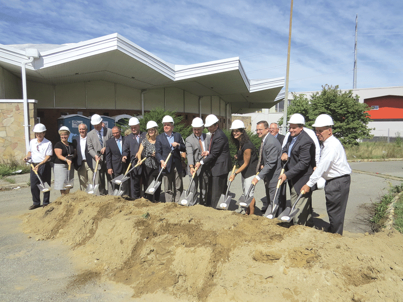 A large group of officials take up shovels for the groundbreaking