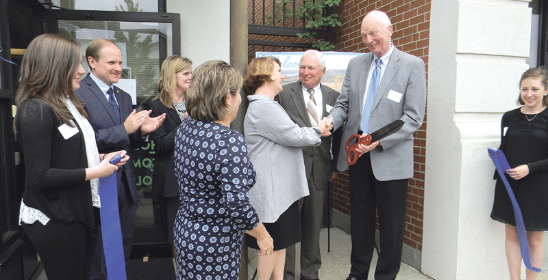 Holyoke Community College President William Messner (far right), who recently retired, shakes hands with Tracy Opalinski during the opening ceremony for the new E2E (Education to Employment) program in Ware.