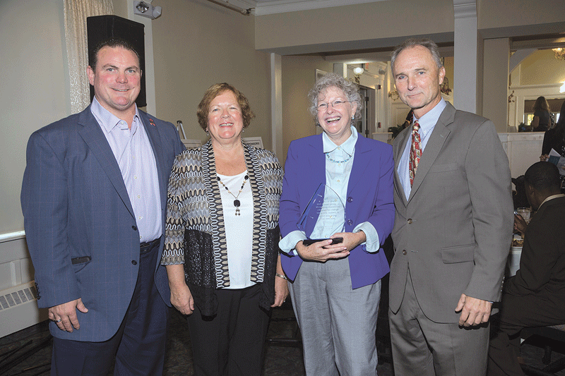 Timm Marini (left), president of HUB International, Carol Tourangeau (second from left), and HRU President Don Kozera present HRU's 2016 Armand Tourangeau Volunteer of the Year Award to Cheryl Rumley of Apex Healthcare.
