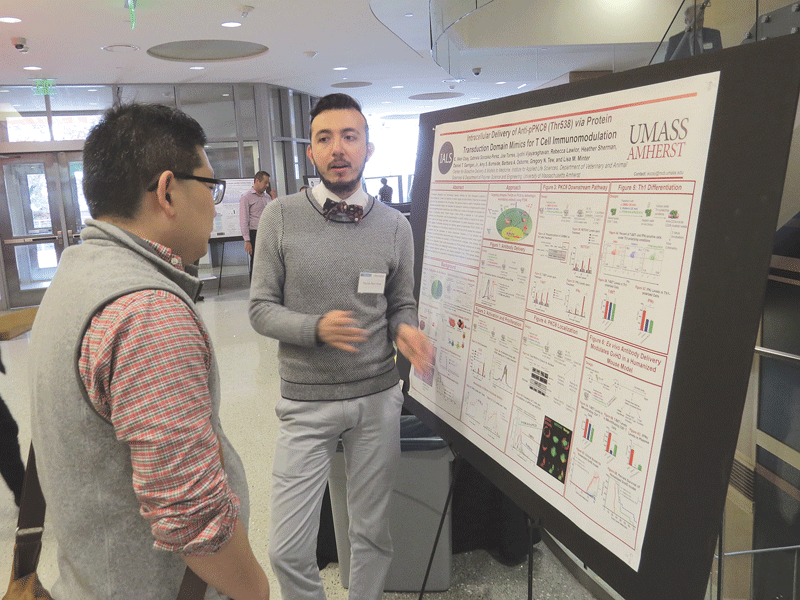 A student displays his research project at the event