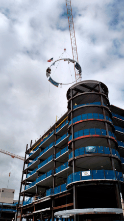 A crane maneuvers the final beam into place atop the future home of HGM Springfield.