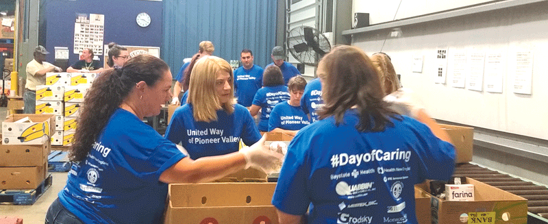 A group of 15 volunteers from AAA of Pioneer Valley, led by Tammi Benson, sort through various donated food items at The Food Bank of Western Massachusetts in Hatfield