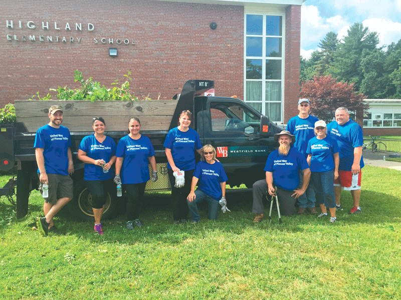 A group of volunteers from Westfield Bank show off a hard day's work spent doing landscaping projects at Highland Elementary School in Westfield; and Marco Gomes of MassMutual works diligently on a painting project at the Boys and Girls Club of Greater Holyoke