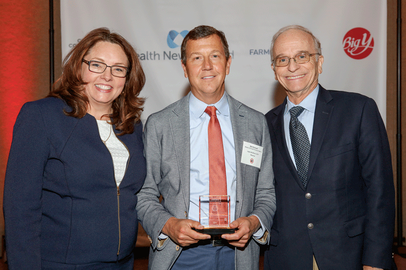 Bill Grinnell (center), president of Webber & Grinnell Insurance, a winner in the Total Revenue category, accepts his plaque from Ashley Allen, vice president of Sales & Marketing for Health New England, the presenting sponsor, and Don D'Amour, chairman of Big Y Foods, a platinum sponsor