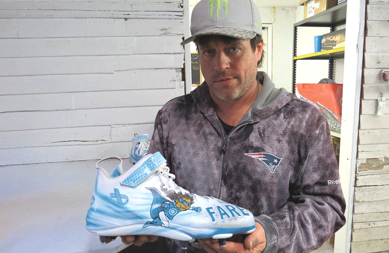 Joe Ventura holds the cleat he made for Patriots defensive lineman Alan Branch for the 'My Cleats, My Cause' program.