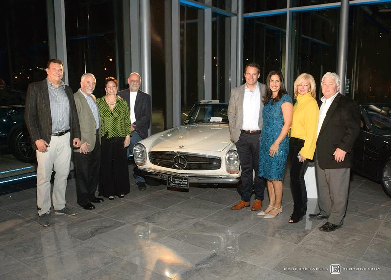 Guests gather around a vintage SL Mercedes model