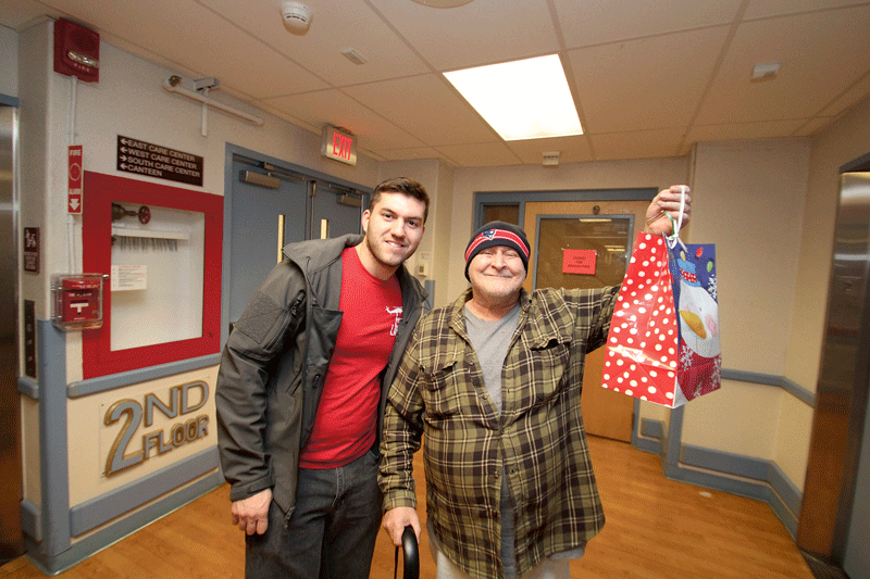 HCC students Jonathan Jasmin delivering holiday gift bags to Soldiers' Home residents