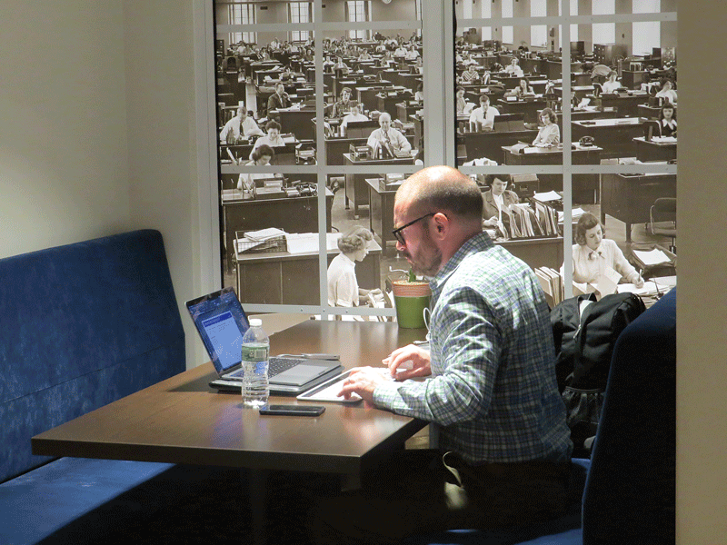 "A MassMutual employee gets some work done in front of an image that Roger Crandall calls ""a look back in time."""