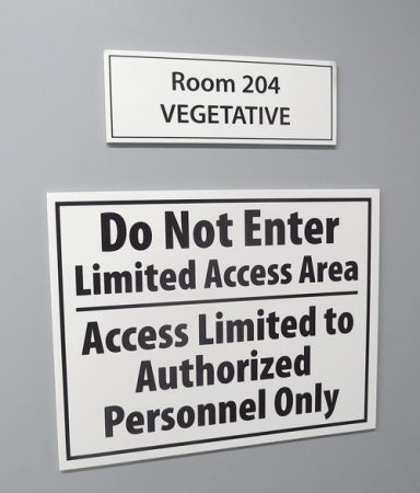 The sign outside one of the growing rooms conveys the importance of keeping the plants safe at GTI's Holyoke facility.v