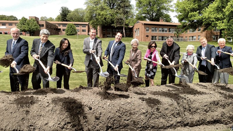 Officials take up ceremonial shovels during the groundbreaking for Hillside Residence on May 18.