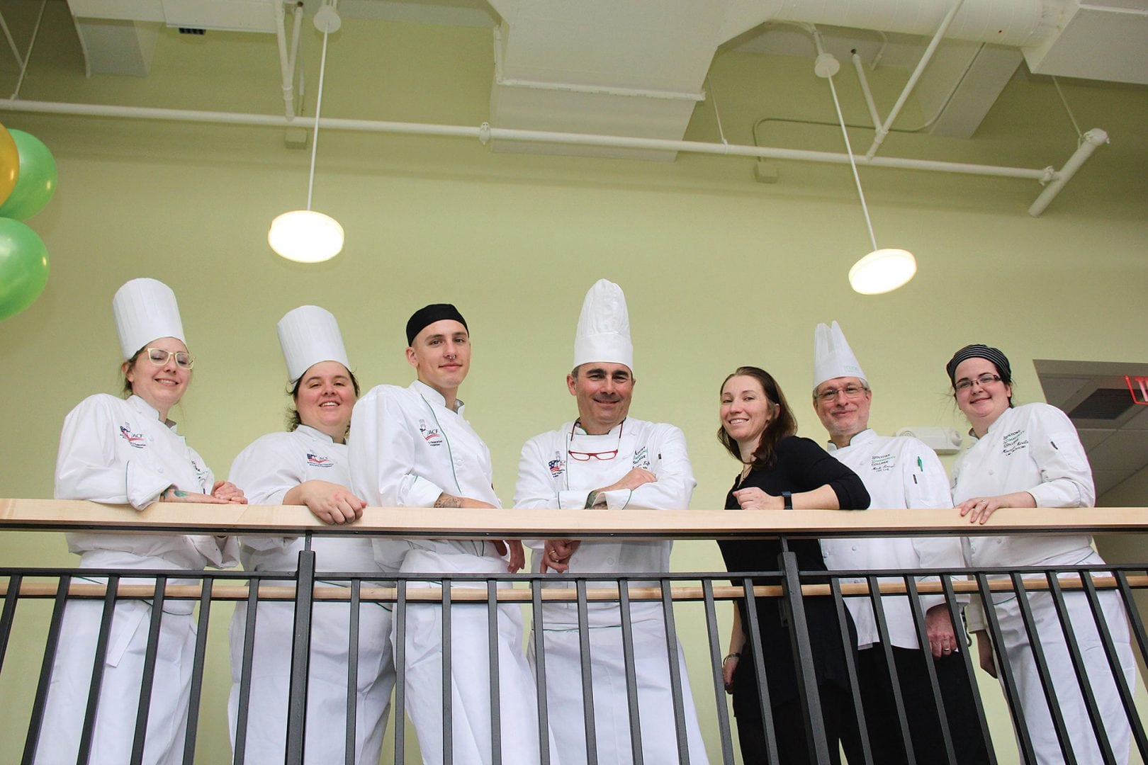 faculty and staff stand on the second-floor landing of the new HCC MGM Culinary Arts Institute