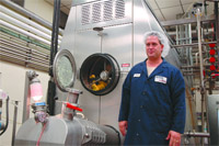 Lenny Dion, butter room manager at Agri-Mark's West Springfield plant, next to one of the largest butter churns in the world.