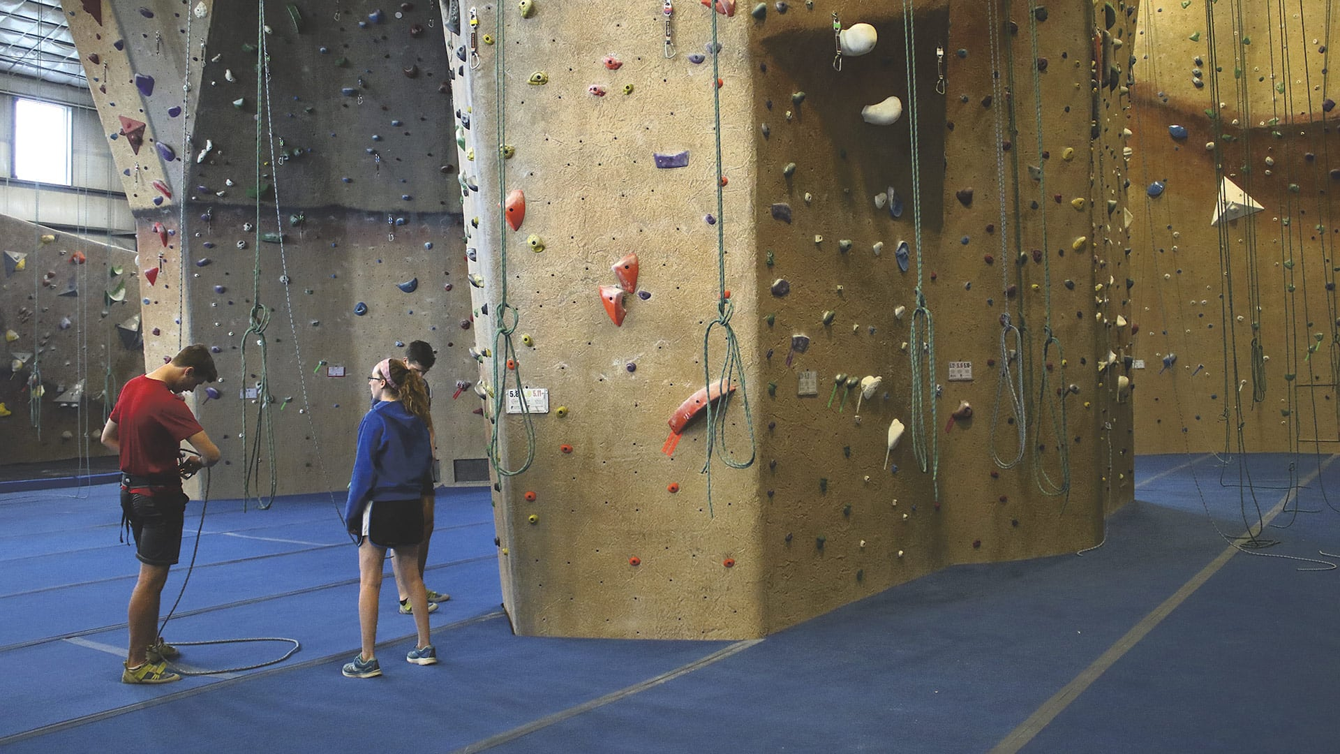Climbers prepare to scale the high walls at Central Rock Gym.
