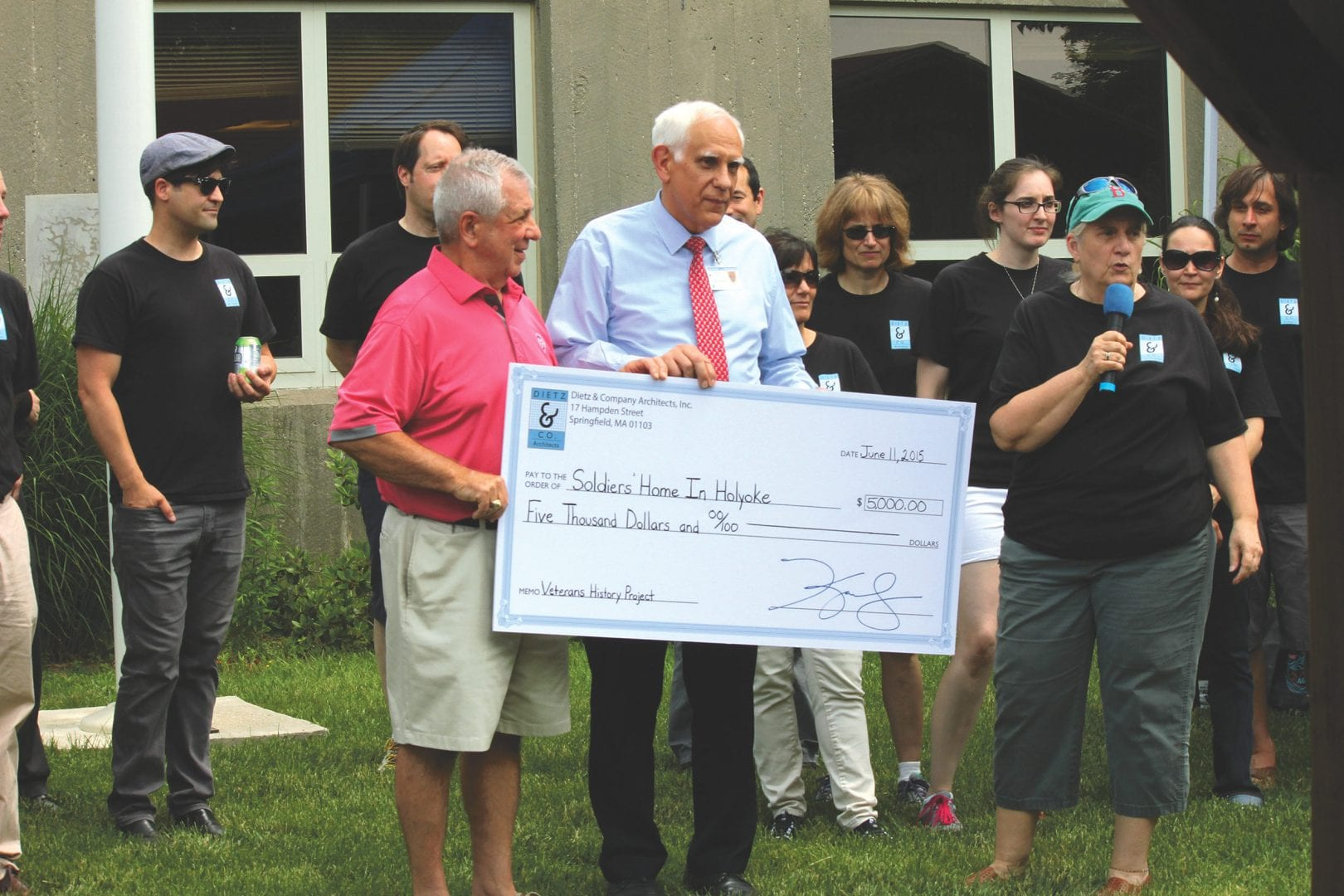 Kerry Dietz, right, presents a donation to the Soldiers' Home in Holyoke as part of her company's 30th anniversary celebration. Several staff members are in the background.