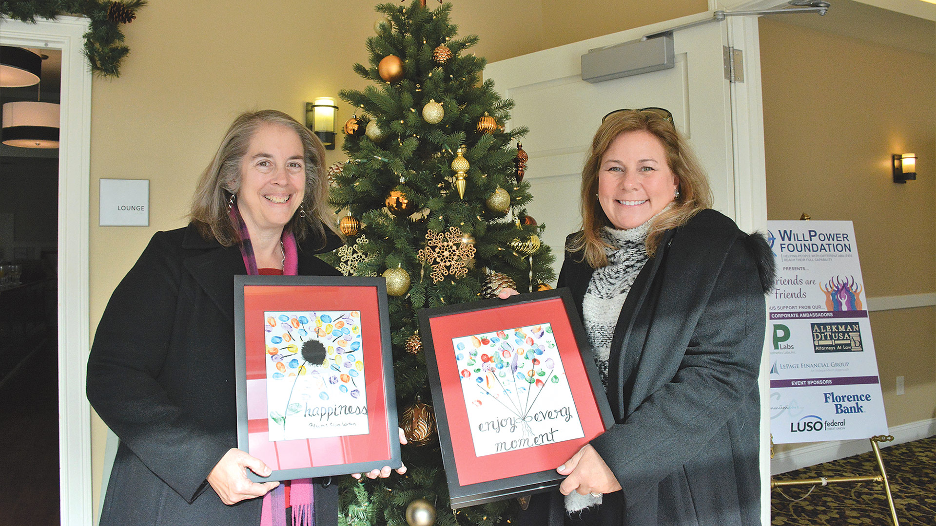 Sharon Dufour of LUSO Federal Credit Union and Kim Anderson with art they won at the auction.