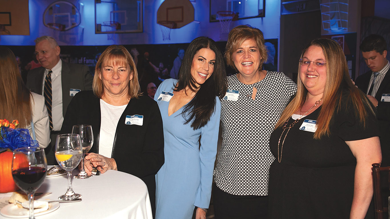Consolidated Health Plans President and CEO, Drew DiGiorgio, right, with company founder Kevin Saremi at CHP's recent 25th anniversary celebration at the Basketball Hall of Fame. At left: from left, CHP employees Maureen Brunelle, Karen O'Connor, Susan Daley, and Amanda Noel.