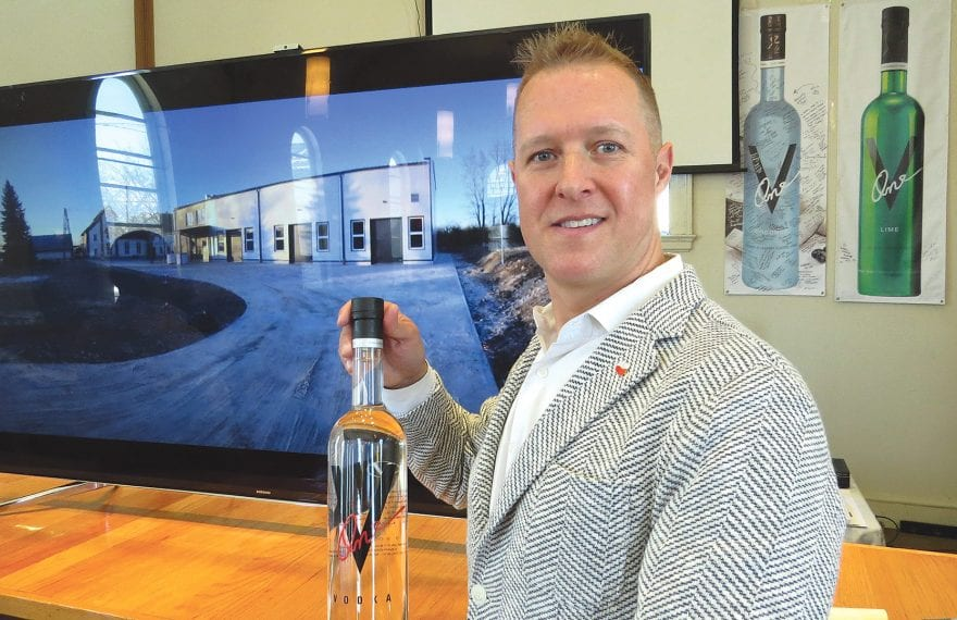 Paul Kozub stands in front of picture of his new distillery in Poland.