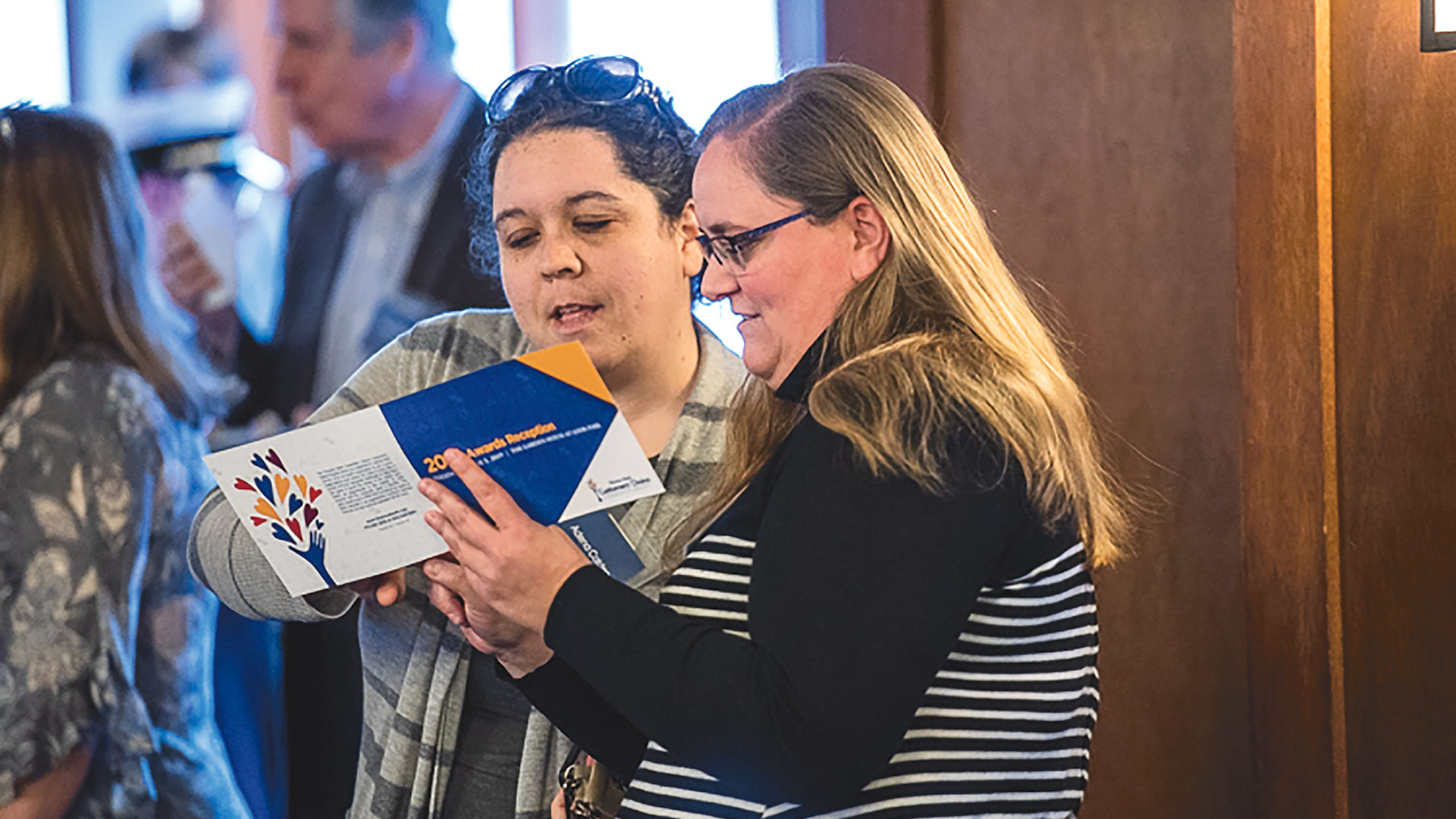 Adena Calden, left, and Kate Agresto, both of the Leeds Elementary Parent Teacher Organization, read the brochure outlining the award recipients