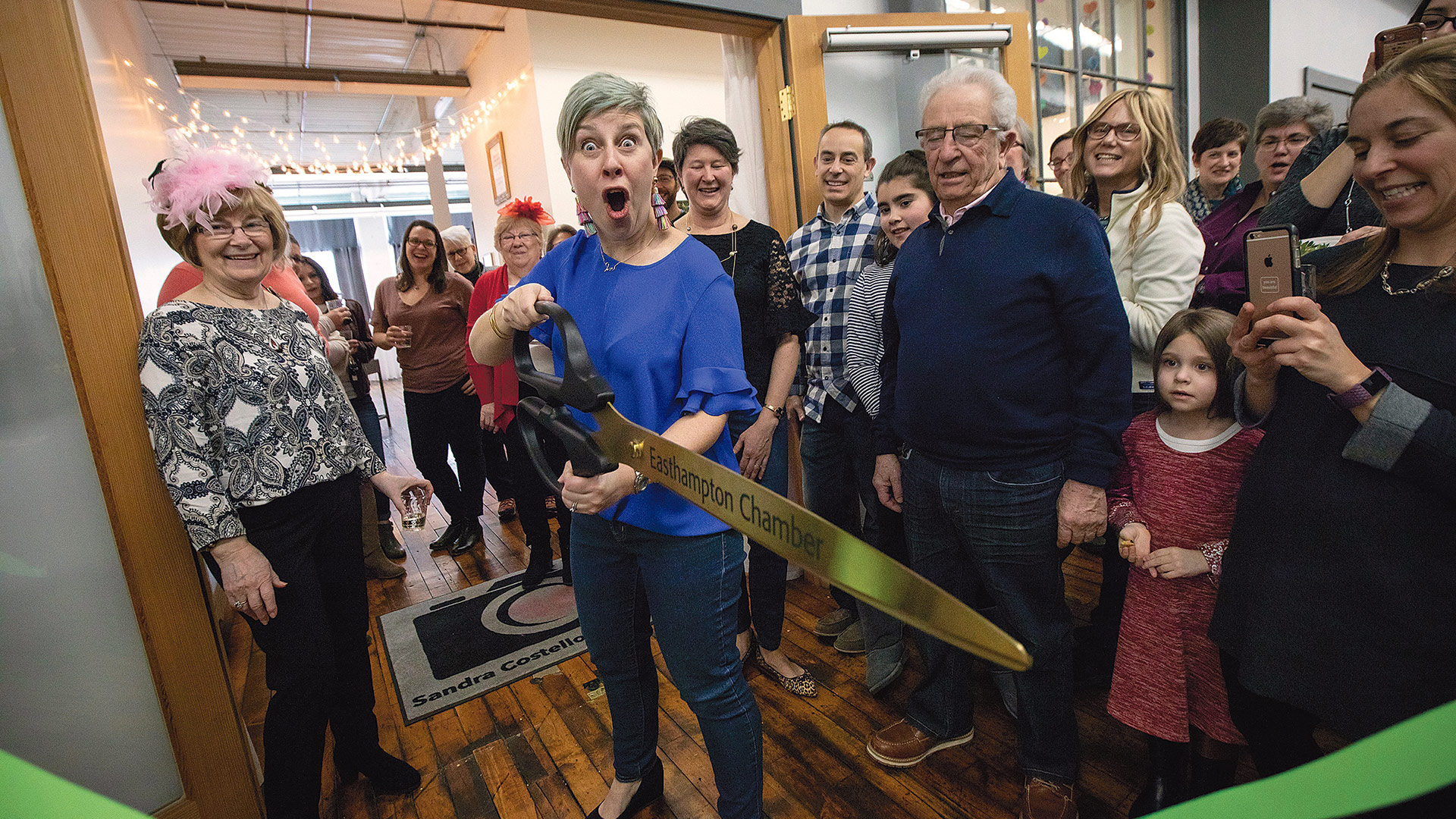 Sandra Costello, owner of Sandra Costello Photography, cuts the ribbon to the opening of her new photography studio in the Eastworks Building in Easthampton on Feb. 17. Surrounded by family, friends, and clients, Costello celebrated her new space for capturing portraits of women, families, high-school seniors, and professionals. (Photo by Ryan Williams)