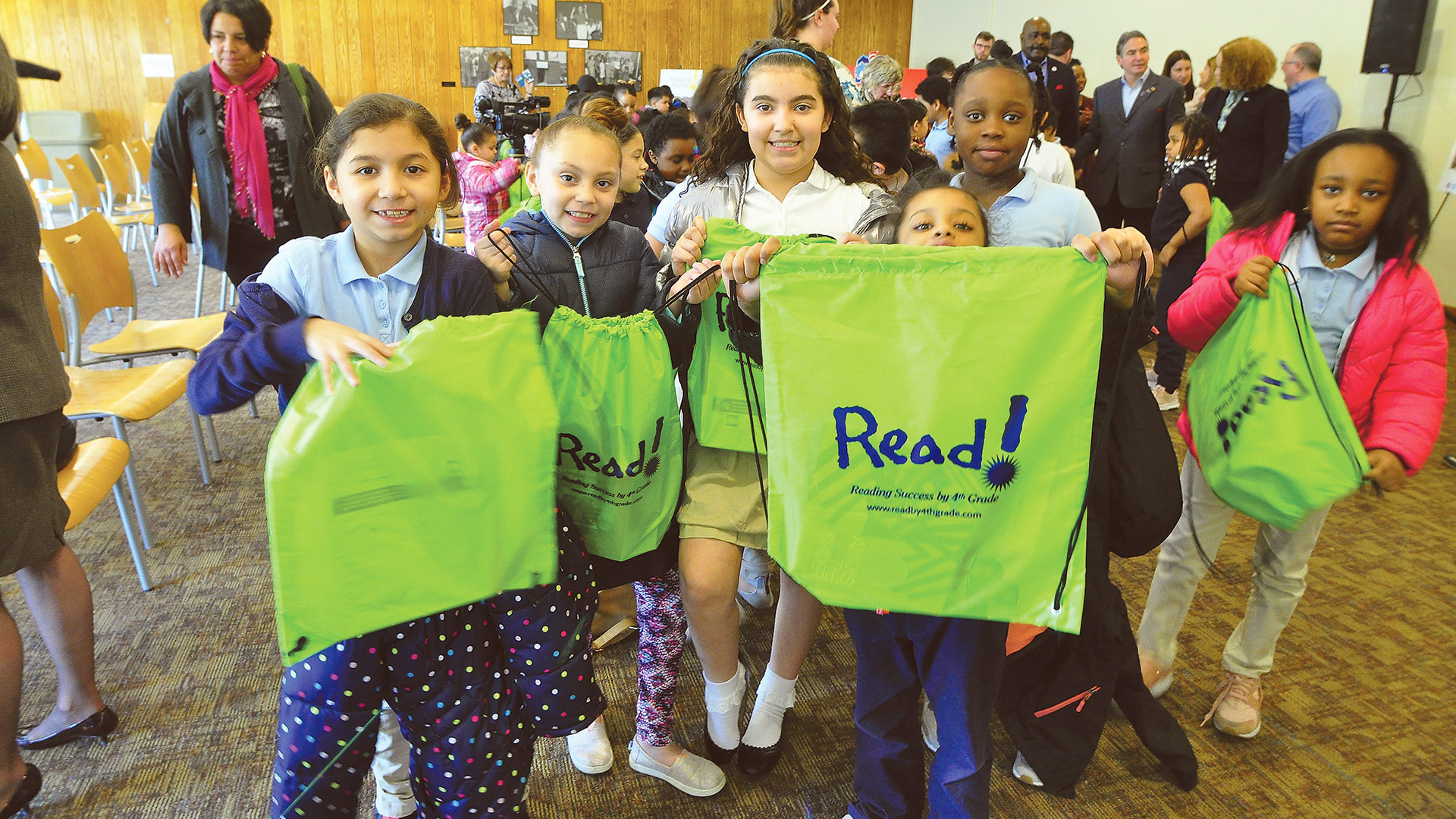 Students from DeBerry pose with the book bags, filled with books, that they received
