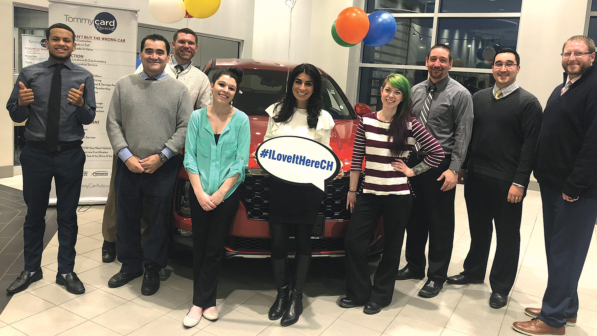 Carla Cosenzi, center, joins staff at the dealership in celebrating the honor.