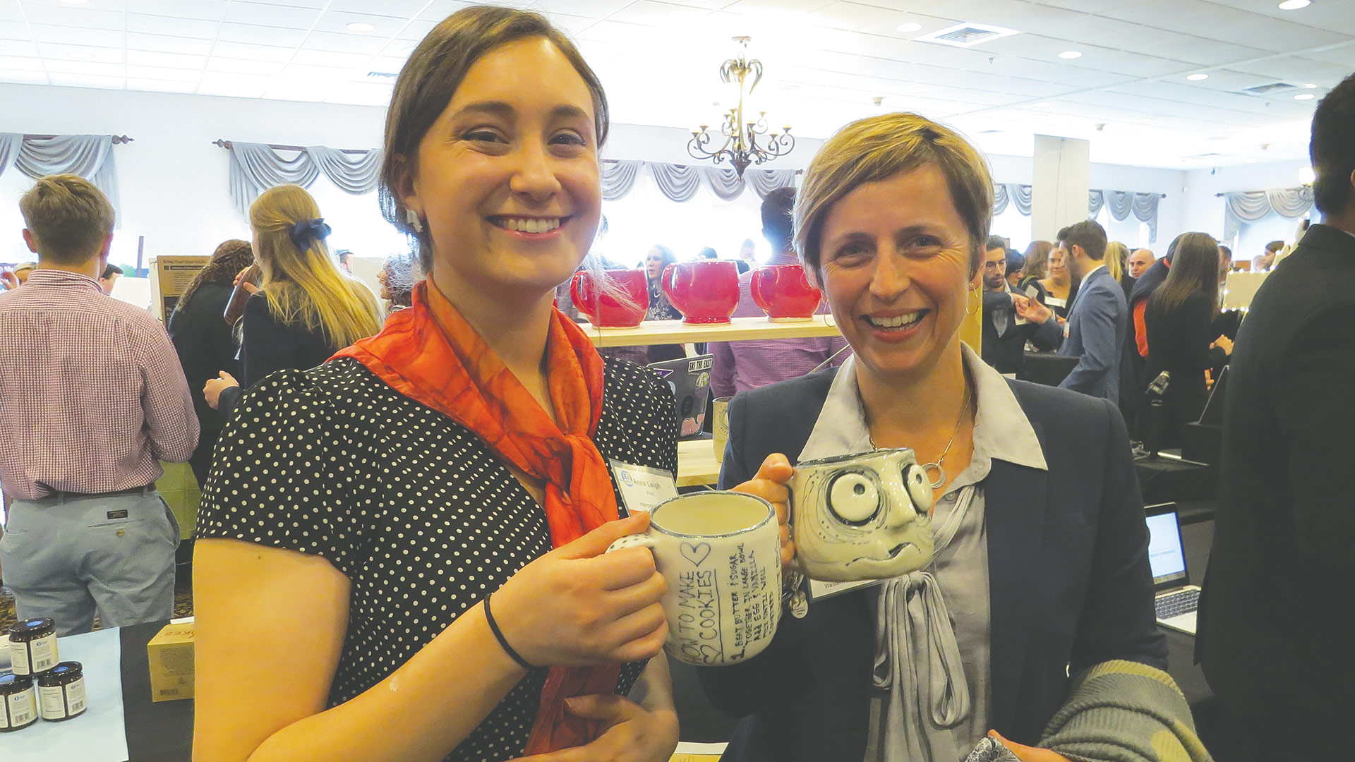 Anna Aron (left), a Hampshire College student and founder of Anna Leigh Pottery, shows some of her works to Katie Allan Zobel, president and CEO of the Community Foundation