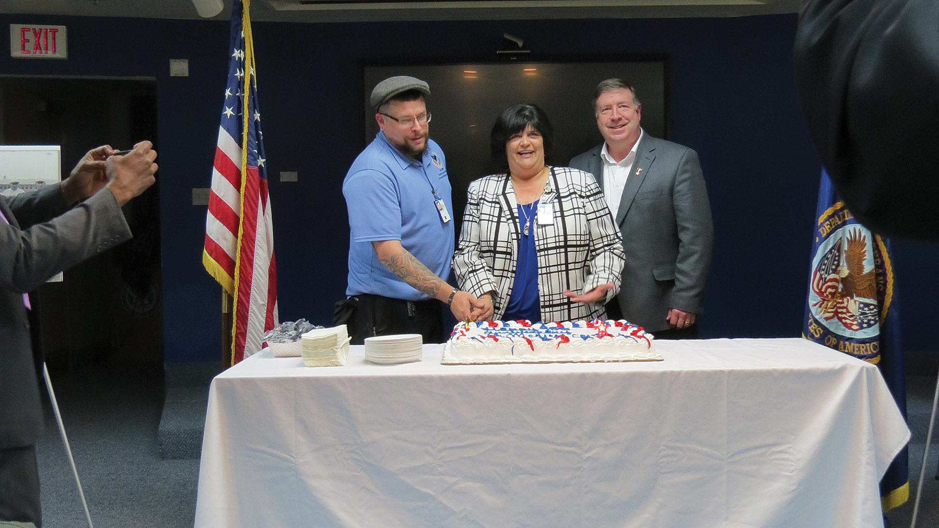 Collins joins recently hired employees to cut the cake