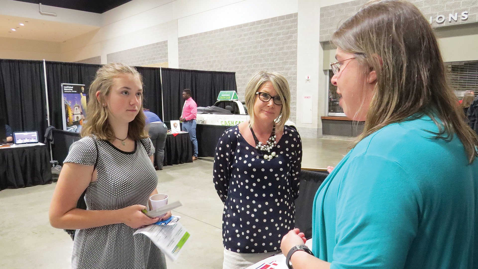Kristin Carlson, president of Peerless Precision, talks with a student about opportunities in manufacturing while Dawn Creighton, Western Mass. Director for AIM, listens in