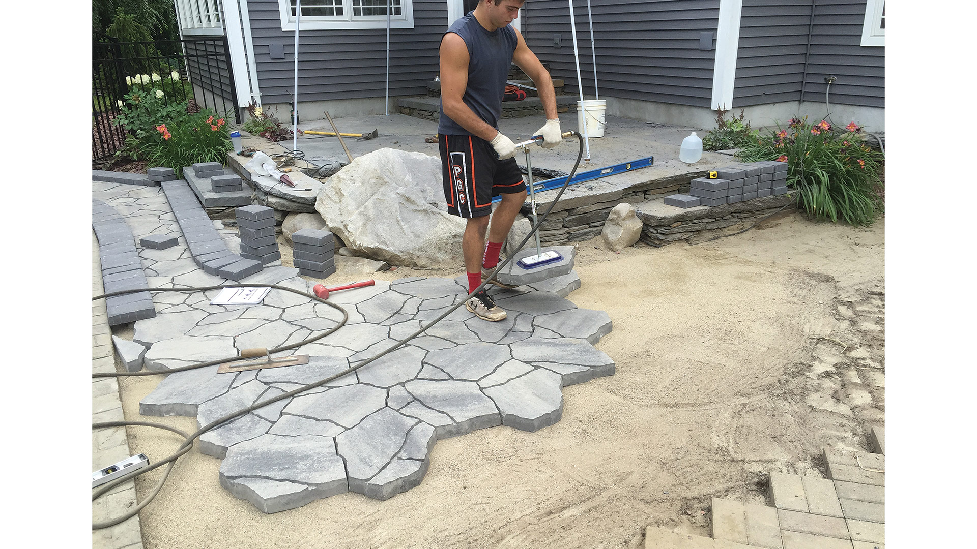 A worker with Pioneer Landscaping places patio stones.