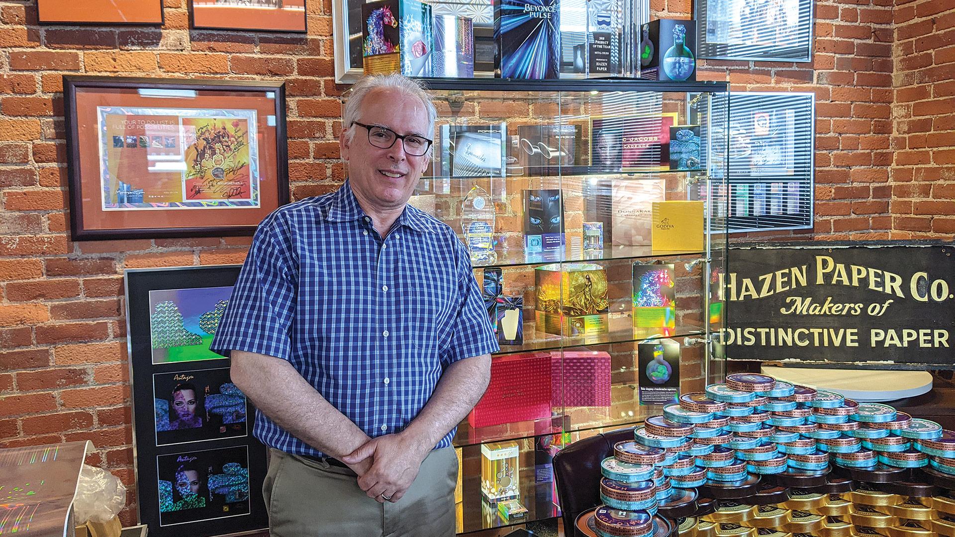 John Hazen stands beside displays