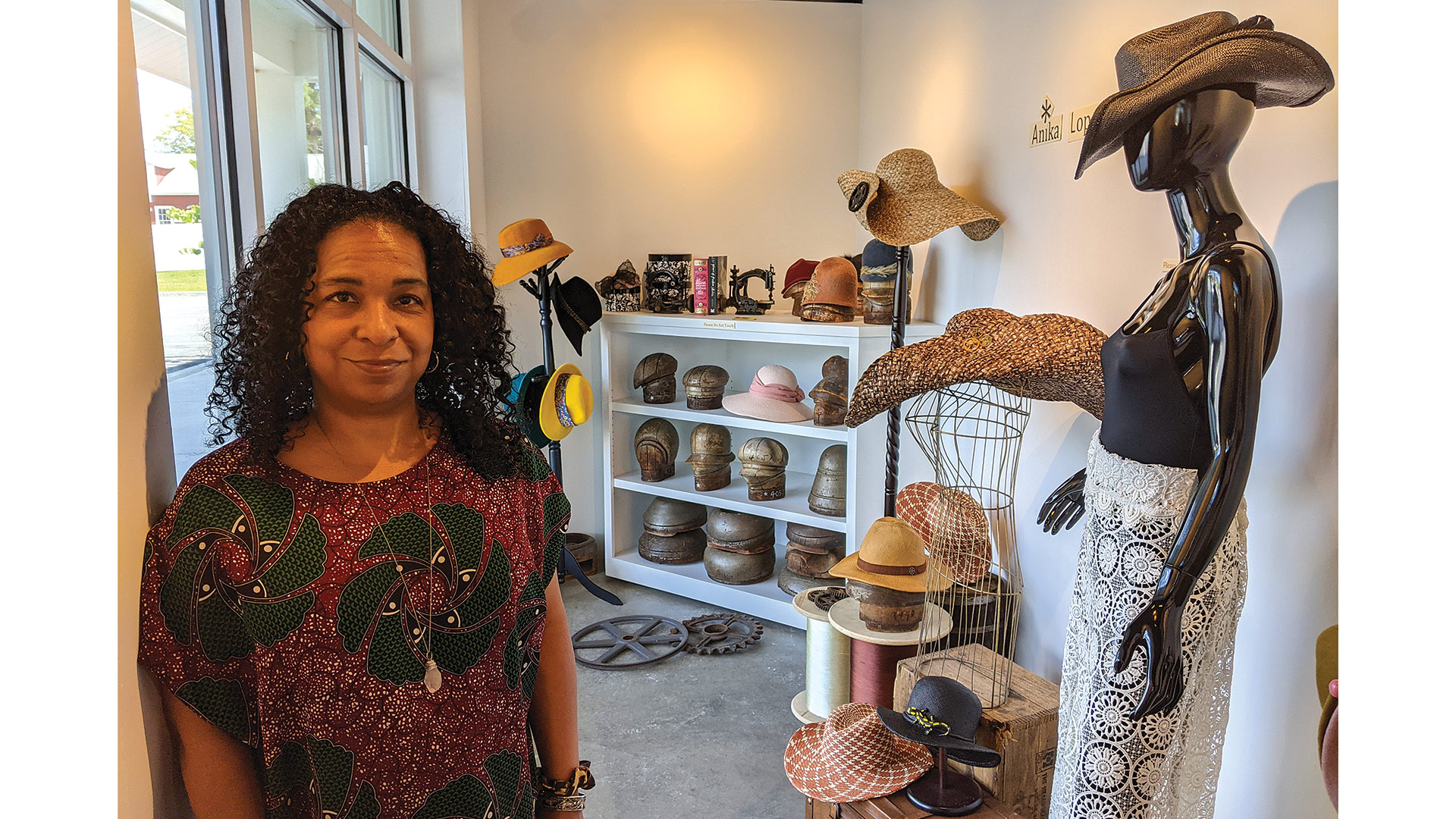 Anika Lopes with the front-window display of her millinery art.